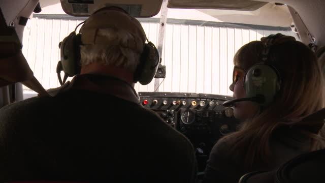 CU Mature pilot and passenger taking headsets off at hangar / Flathead, Montana, USA