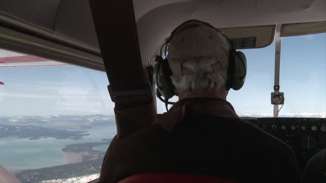 aerial cu slo mo mature pilot flying over flathead lake in small aircraft / flathead, montana, usa - piloting stock videos and b-roll footage