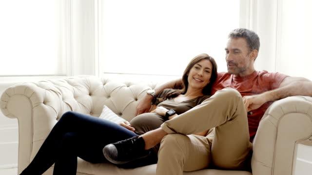vidéos et rushes de mature couple enceinte assise sur canapé à la maison - être à l'aise