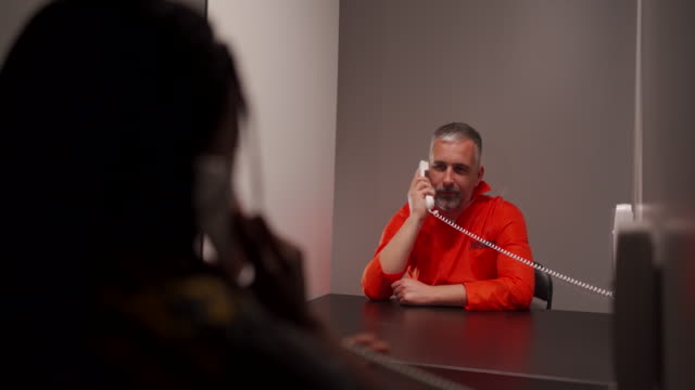 mature prisoner in jumpsuit talking with his wife in visit room at prison - prison jumpsuit stock videos & royalty-free footage