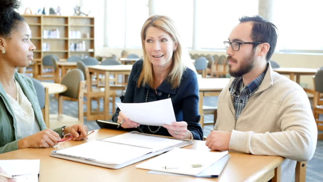Mature professor explaining something to diverse study group