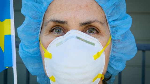 mature serious overworked, female matute health care worker holding a swedish flag - swedish culture stock videos & royalty-free footage