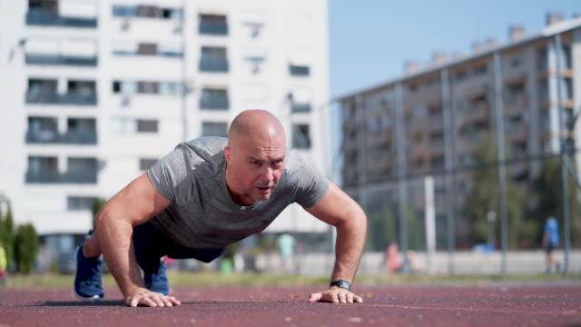 vídeos de stock e filmes b-roll de mature sportsman doing push-ups - careca