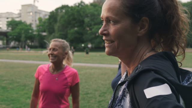 mature sporty woman smiling while looking away by friends at park - 55 59 år bildbanksvideor och videomaterial från bakom kulisserna