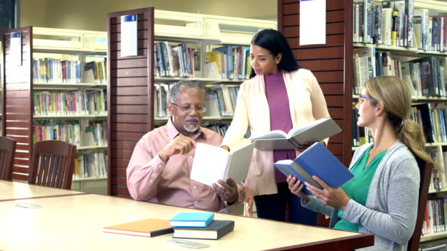 mature students studying in library with instructor - librarian stock videos & royalty-free footage