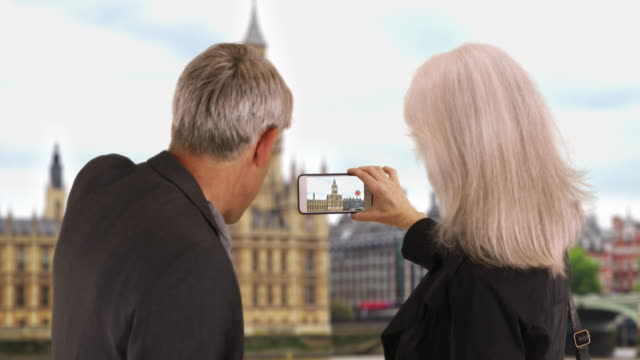 mature tourist couple taking video of big ben - big ben点の映像素材/bロール