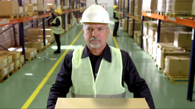 Mature Warehouse Employee Handing Over A Box