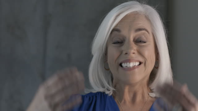 Mature, white haired businesswoman gestures to camera with open arms