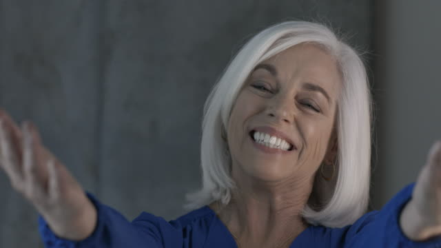 mature, white haired businesswoman gestures to camera with open arms - arms outstretched stock videos and b-roll footage