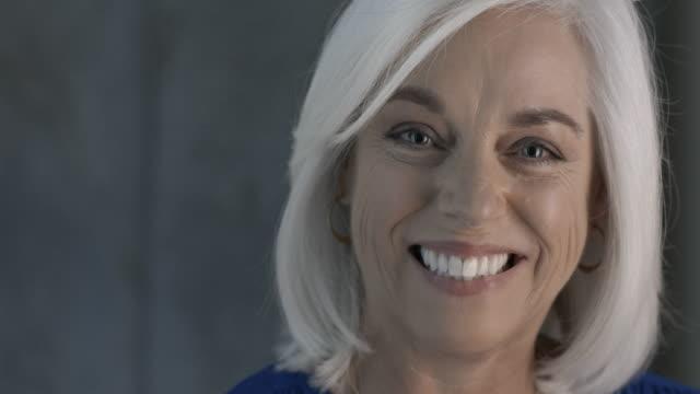 vídeos de stock, filmes e b-roll de mature, white haired businesswoman smiling to camera - cabelo de comprimento médio