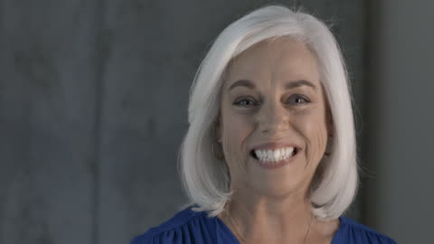 mature, white haired businesswoman smiling to camera - white hair stock videos & royalty-free footage