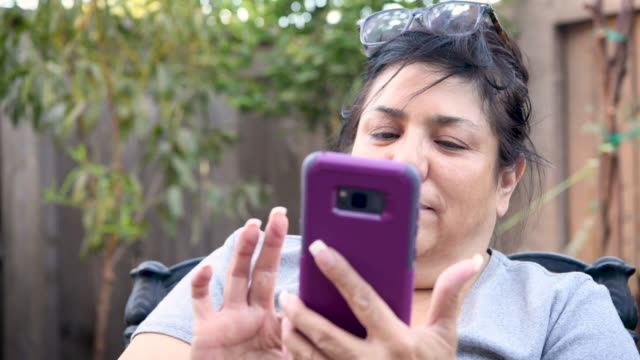 mature woma using her smart phone sitting at her backyard - brown hair stock videos & royalty-free footage