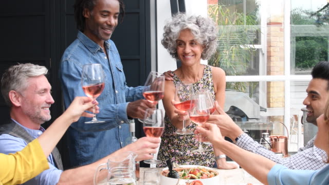 Mature woman and man raising their glasses with group of friends at dinner party