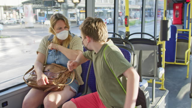 mature woman and schoolboy meeting and greeting with elbows in public transportation city bus and both wearing face masks to prevent infection with contagious virus. - öffentliches verkehrsmittel stock-videos und b-roll-filmmaterial