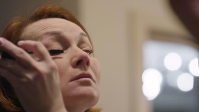 Mature woman applying mascara before mirror