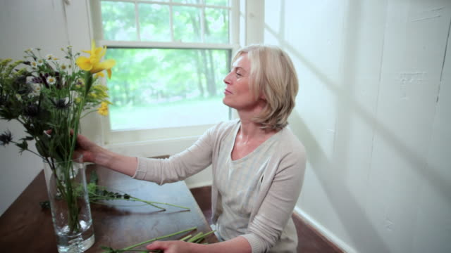 Mature woman arranging flowers