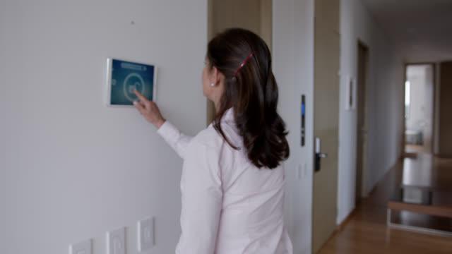 vídeos de stock, filmes e b-roll de mulher madura em casa ativando bloqueio de segurança em sua casa inteligente a partir de tablet - ir embora