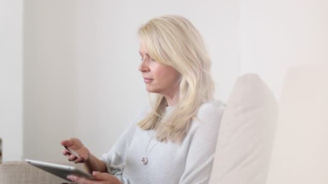 vídeos y material grabado en eventos de stock de mature woman at home using digital tablet and credit card - pago por móvil