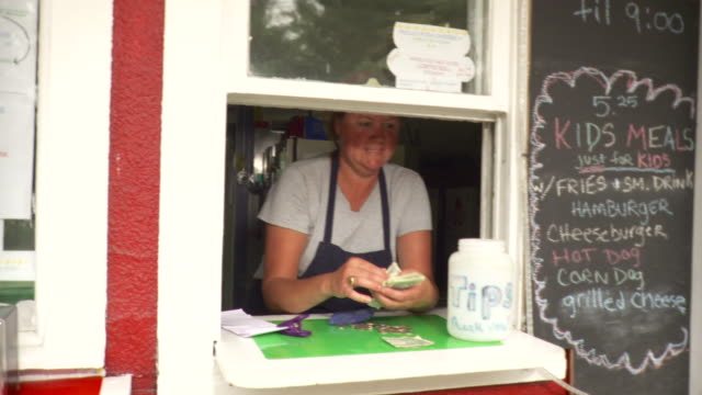 ms zo mature woman at ice cream stand counting money / stowe, vermont, usa - gratuity stock videos & royalty-free footage