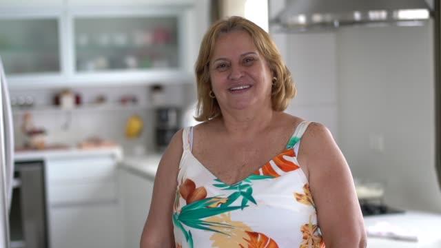 vídeos de stock e filmes b-roll de mature woman at kitchen portrait - domestic kitchen