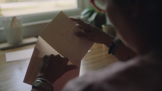vídeos de stock, filmes e b-roll de cu slo mo. mature woman at stationery desk places personal letter into envelope to mail. - sending