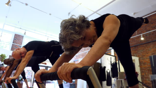 vídeos de stock, filmes e b-roll de ms tu mature woman balancing on pilates reformer during class in exercise studio - active seniors