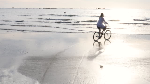 vidéos et rushes de bicyclettes mûres de femme le long de l'appartement de marée au lever de soleil - 55 59 ans
