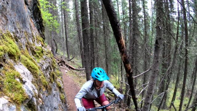 vídeos de stock e filmes b-roll de mature woman bikes along forest pathway - só uma mulher madura
