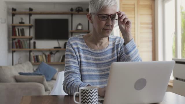 vidéos et rushes de mature femme blogging sur son portable à la maison et en regardant la caméra. - femmes d'âge mûr