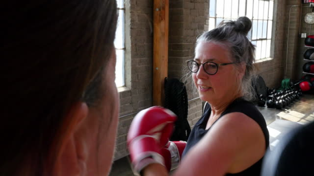 ms pan mature woman boxing with coach in gym - gym stock videos & royalty-free footage