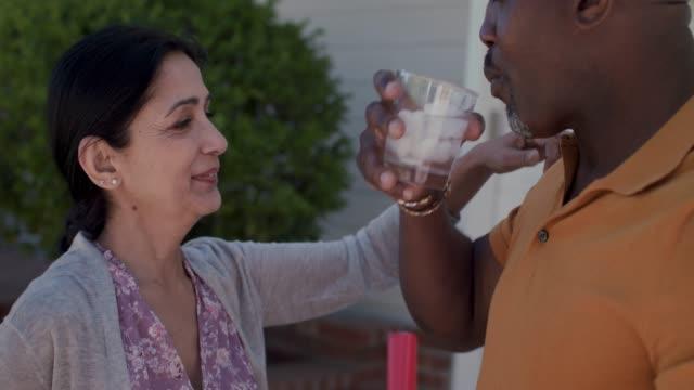vidéos et rushes de mature woman brings drink to her husband who sweeps driveway - eau potable