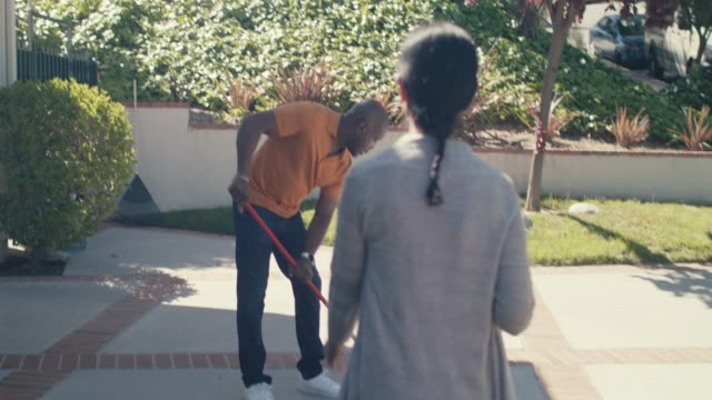 mature woman brings drink to her husband who sweeps driveway - mature couple stock videos & royalty-free footage