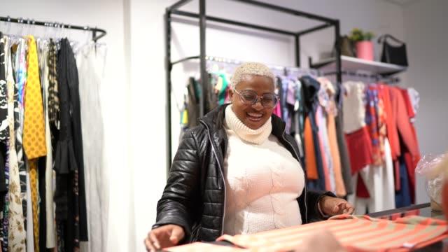 vídeos y material grabado en eventos de stock de mujer madura comprando ropa en una tienda - 40 seconds or greater