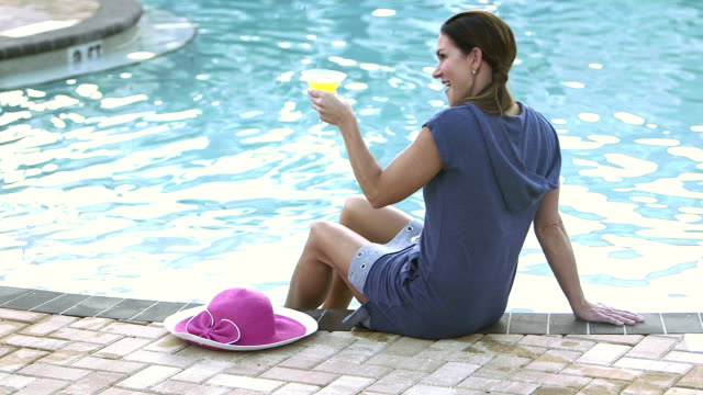 mature woman by swimming pool with a drink - margaritas stock videos and b-roll footage