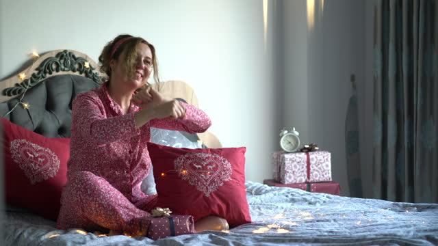 vídeos de stock, filmes e b-roll de mulher madura celebrando a véspera de natal em seu quarto. - só uma mulher madura