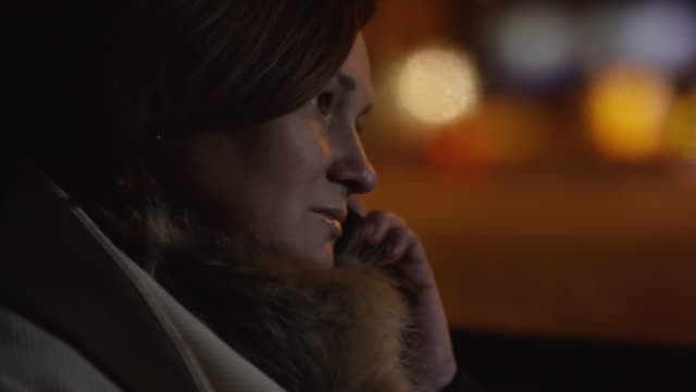 mature woman chatting on mobile phone in moving car - part of a series stock-videos und b-roll-filmmaterial