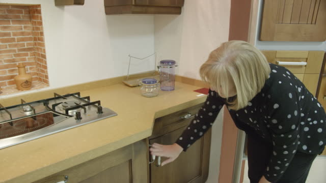 MS T/U mature woman checking build quality of furniture in a kitchen showroom