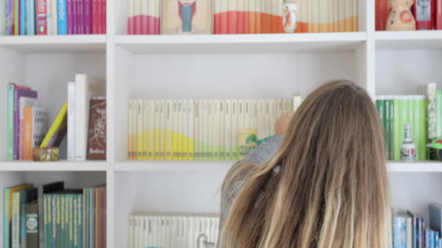 vidéos et rushes de mature femme choisissant un livre à lire dans une étagère - collection
