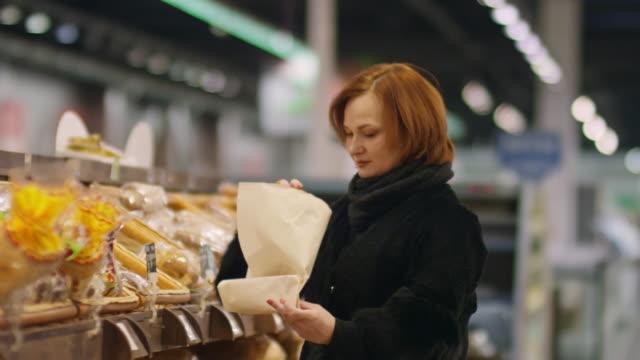 vídeos de stock e filmes b-roll de mature woman choosing fresh bread in supermarket - pão