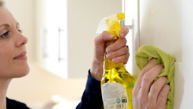 Mature Woman Cleaning Kitchen Cupboards At Home