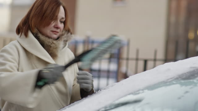mature woman cleaning snow from car in winter - winter coat stock videos & royalty-free footage
