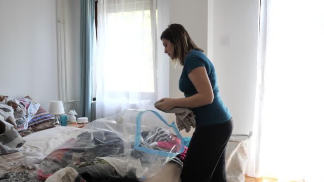 stockvideo's en b-roll-footage met rijpe vrouw die de kast schoonmaakt en de kleren van het laatste jaar onderzoekt - chaos