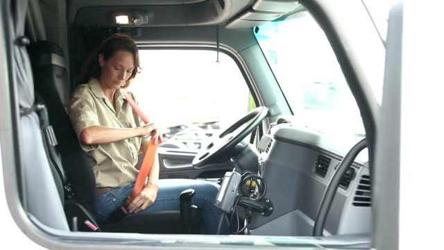 Mature woman climbing into cab of semi-truck