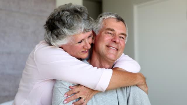 Mature woman cuddling her husband