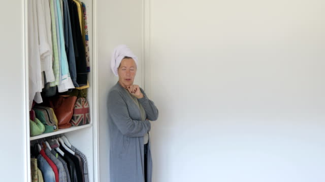 mature woman deciding what to wear - wardrobe stock videos & royalty-free footage