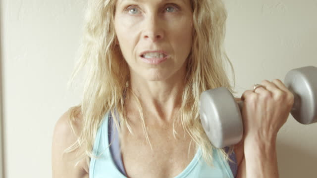 a mature woman does curls in her home gym. - flexing muscles stock videos and b-roll footage