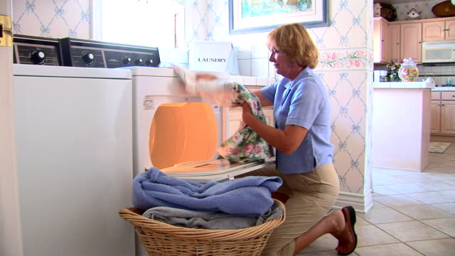 stockvideo's en b-roll-footage met mature woman doing laundry - alleen oudere vrouwen