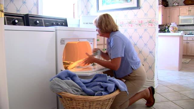 mature woman doing laundry - 衣類乾燥機点の映像素材/bロール