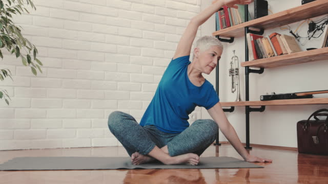 mature woman doing relaxation exercises at home. - exercising stock videos & royalty-free footage