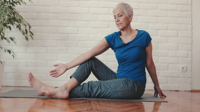 mature woman doing relaxation exercises while practicing at home. - exercise equipment stock videos and b-roll footage